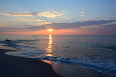 Sunrise Over Ocean with Reflecting Rays and Pastel Skies. The sunrises over the ocean on a summer morning Stock Photography