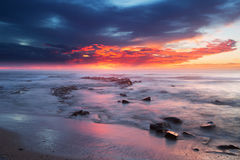 Sunrise over the ocean with rocks and water in foreground Stock Photography