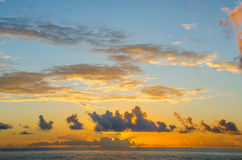 Sunrise over the ocean. The sun rises behind clouds over the ocean Royalty Free Stock Images