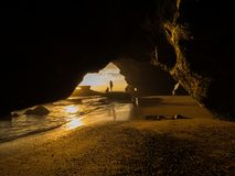 Sunrise over the ocean. Sun rising over the ocean from within a cave located on the sea shore on a summer day lighting up the sky in red and orange colours Stock Images