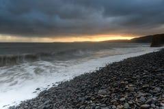Sunrise over the ocean. Sunrise at Clovelly beach in Devon Stock Image