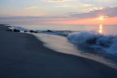 Sunrise Over Ocean with Waves Crashing. The sunrises over the ocean early in the morning with waves crashing onto the shore Stock Photo
