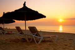 Sunrise over the parasol on the beach, Tunisia Stock Photo