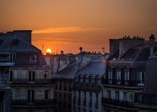Sunrise over Paris roof tops. Sun rising above historic Paris roof tops and chimneys Stock Image