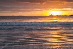Sunrise over pier in bay Stock Photo