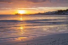 Sunrise over pier in bay Stock Image