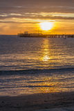 Sunrise over pier in bay Stock Photos