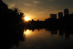 Sunrise over pond at park in a city. Silhouette tree and building against with sunrise, orange sky and sun ray.  Stock Photography