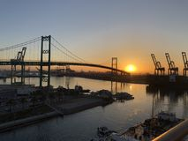 Sunrise over the Port of Los Angeles. Early morning sunrise over the port of Los Angeles showing cranes and a bridge Stock Images