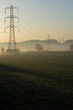 Sunrise over pylon field. Electricity pylons at sunrise in a rural field Royalty Free Stock Image