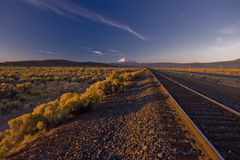 Sunrise over a railroad leading into the mountains. Sunrise with a large snow capped Mountain in the distance stock image