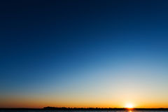 Sunrise over river in blue sky Royalty Free Stock Photo