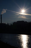 Sunrise over the river. Near the factory. A large factory chimney from which smoke rises. Dark blue sky over the hill Royalty Free Stock Images