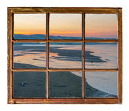 Sunrise over river in Nebraska Sandhills. As seen through a vintage, grunge, sash window with dirty glass Royalty Free Stock Photos