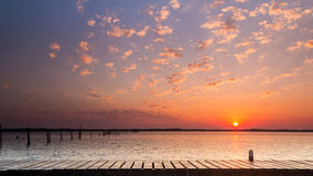 Sunrise over river with wooden porch Royalty Free Stock Images