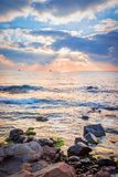 Sunrise over a rocky beach. Colorful clouds reflecting in the sea Royalty Free Stock Image