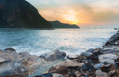 Sunrise over rocky beach and mountain background Stock Photo
