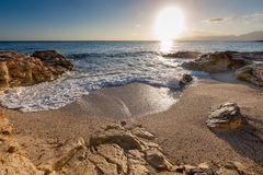 Sunrise over a rocky inlet with gentle surf. Breaking on the sand as the bright fiery orb of the sun rises slowly in the clear blue summer sky stock image