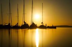 Sunrise over sailboats stock images