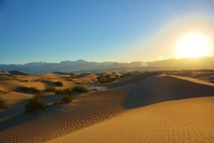 Sunrise over sand dunes and mountains royalty free stock photo