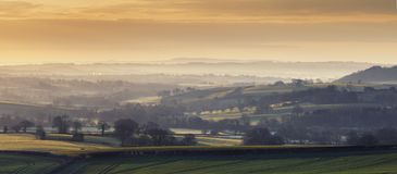 Sunrise over Scenic Farming Fields in UK. Panorama of British farming fields in sunrise light at spring in Much Wenlock, Shropshire, UK Stock Photo