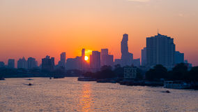 Sunrise over the scenic skyline at Bangkok, Thailand, viewed in backlight at sunrise with orange red clear sky. Boats cruising on Stock Photos
