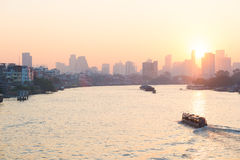 Sunrise over the scenic skyline at Bangkok, Thailand, viewed in backlight at sunrise with orange red clear sky. Boats cruising on Stock Photo