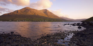 Sunrise over Scottish Loch. Orange tinted clouds shroud the tops of distant mountains reflected in the calm water of Loch Sligachan on the Isle of Skye, Scotland Stock Images
