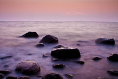 Sunrise over the sea. Stones in water stock photography