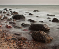 Sunrise over the sea. Stones in water royalty free stock image