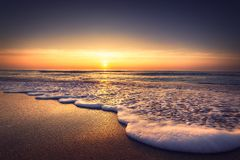 Sunrise over the sea and beach. Waves washing the sand.  royalty free stock image