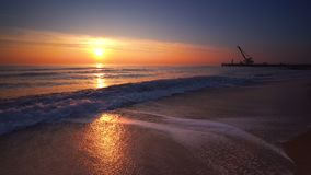 Sunrise over the sea and beach. Waves washing the sand. stock footage