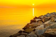 Sunrise over sea. Beautiful colorful sunrise over sea and boulders Stock Photo