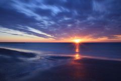Sunrise over sea. Beautiful summer sunrise over sea with moving clouds. Long term exposure Royalty Free Stock Images