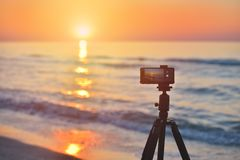 Sunrise over the sea coast. Fireball of the sun above the horizo. N in a colorful orange sky. Smartphone camera on a tripod in the foreground Stock Photo