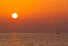 Sunrise over the sea and fishing boat Stock Photos