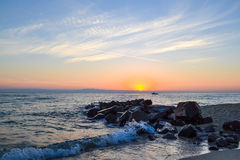 Sunrise over the sea. Large stones and the oncoming wave Royalty Free Stock Photography