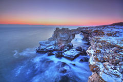 Sunrise over the sea and rocky shore Stock Images