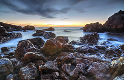 Sunrise over the sea and rocky shore Stock Photos