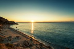 Sunrise over beach in Greece. Sunrise over the sea, the rolling calm waves in Greece Stock Image