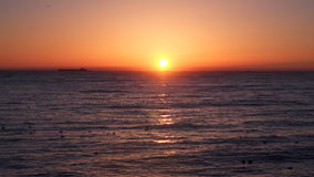 Sunrise over the sea. We see a cargo ship on the horizon.  stock video
