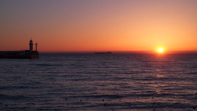 Sunrise over the sea. We see a cargo ship on the horizon. Pier with a beacon.  stock video footage