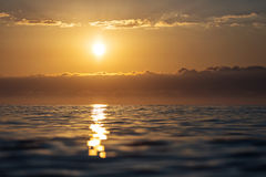 Sunrise over a sea with small waves and beautiful clouds in back Royalty Free Stock Image