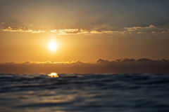 Sunrise over a sea with small waves and beautiful clouds in back Royalty Free Stock Images