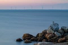 Sunrise over sea and some wind power plants. Stones from pier in foreground Royalty Free Stock Photo