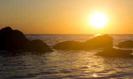 Sunrise over the sea with stones. Pacification and happyness con Royalty Free Stock Photo
