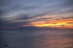Sunrise over the sea with striped clouds. Of pink, orange and blue Royalty Free Stock Images