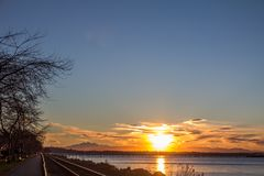 Sunrise over Semiahmoo Bay by the Canada-USA border. Beautiful sunrise with gold, pink, purple and yellow colors over the North Cascade Mountains of Washington royalty free stock images