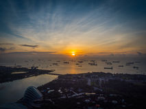 Sunrise over Shipping Lanes in Singapore. The sun rises over the sea in Singapore, reflecting onto many ships dotting the horizon waiting to enter the port Royalty Free Stock Photo