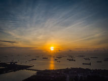 Sunrise over the Shipping Lanes of Singapore. The sun rises over the shipping lanes of Singapore. Ships hauling cargo to and from ports all over the world wait Stock Photography